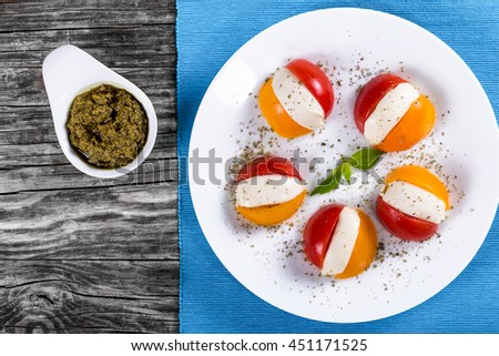 Ð¡aprese salad of red and yellow tomatoes and mozzarella cheese, sprinkled with a mixture of dried Italian herbs and garnished with basil on a white plate, view from above - stock photo