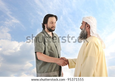 Arab person shaking hands with a businessman - stock photo