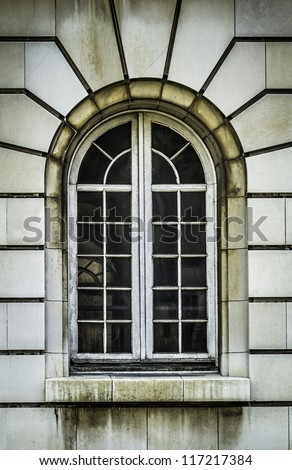 Arch wooden window with stone rustication
