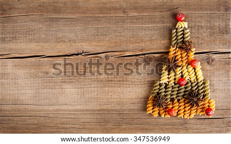 �¡ard with natural decorations on wooden background. Set of different varieties of pasta in the form of a tree. Winter holidays concept