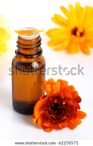 aromatherapy essential oil  with marigold flowers, Isolated white background. Studio shot - stock photo