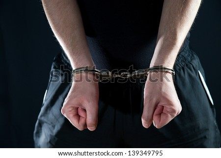 Arrested man handcuffed hands at the back - stock photo