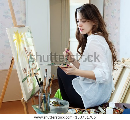 artist paints the house on canvas in studio - stock photo