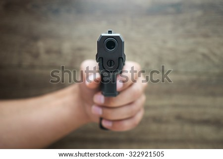 ?asculine hand holding pistol gun, frond wooden background. Violence project. - stock photo