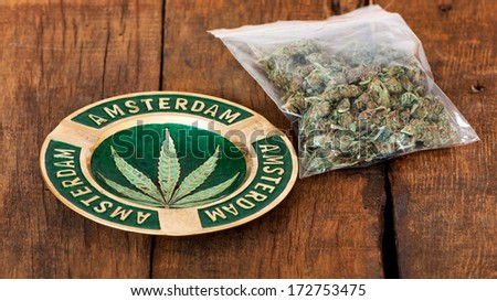 Ashtray with amsterdam sign  and a big plastic bag of weed or marijuana on wooden background - stock photo
