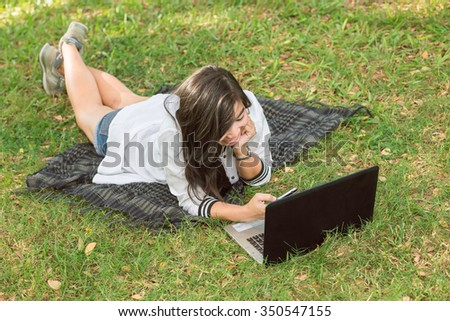 Asia girl on the lawn outside the computer - stock photo