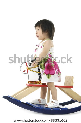 Asian baby on wooden horse - stock photo