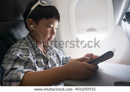 Asian boy use  tablet pc inside aircraft.