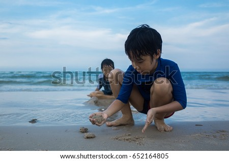 2 Asian boys are playing sand at the beach with the nice blue sky background