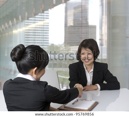 Asian businesswoman shaking hands with colleague - stock photo