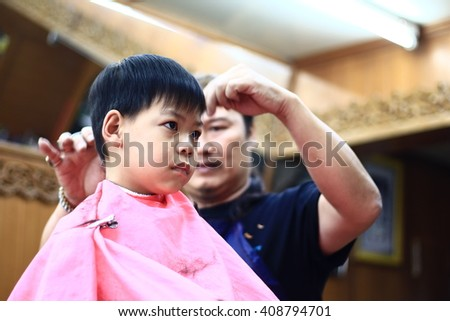 Asian cute boy trying to sit still for a barber in THAILAND.