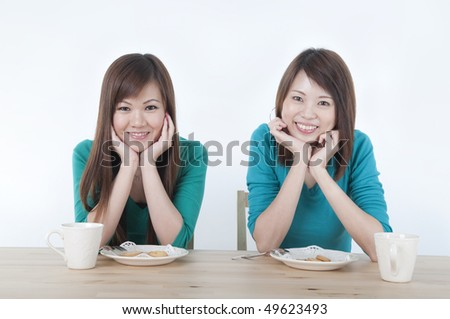 2 asian ethnic girls smieling while healthy eating - stock photo
