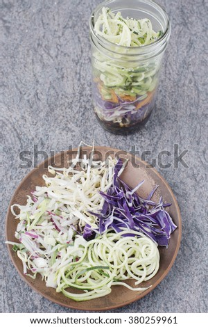Asian inspired mason jar salad with soy sauce, soybean sprouts, radish, cabbage, carrot, edamame and zucchini noodles and its individual ingredients shown on plate  - stock photo