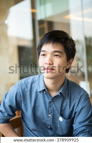 Asian man sitting at coffee shop - stock photo