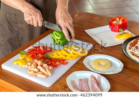 asian woman cooking in the kitchen cutting sweet peppers with a knife.
