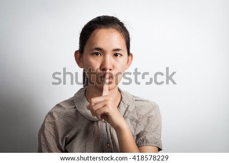 Asian woman finger on her lips. silence gesture. - stock photo