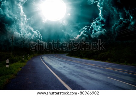 asphalt road and dark thunder clouds over it - stock photo