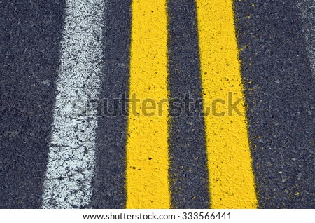 Asphalt road texture with yellow and white stripes. - stock photo