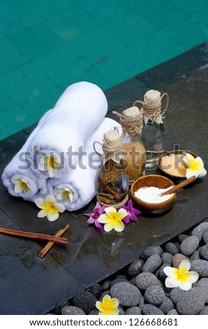 At the Spa, concept in a luxury Villa on Bali Island with, Massage oil, bath-salt, Volcanics stones, body scrub, Towels,Cinnamon sticks, Orchids and frangipani flowers - stock photo