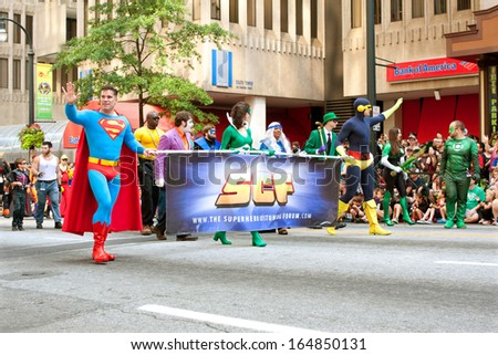 ATLANTA, GA - AUGUST 31:  Superman character carries banner while walking down Peachtree Street in the annual Dragon Con parade, on August 31, 2013 in Atlanta, GA.   - stock photo