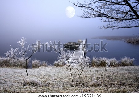 Atmospheric Lake with stunning light as the Moon glows through the Mists onto frozen jetting with Boats during December - stock photo
