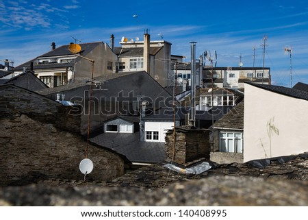 Attics and slate roofs with a variety of satellite dishes, television and chimneys seen from balcony of focus. On a blue background. Lugo. Galicia. Spain - stock photo
