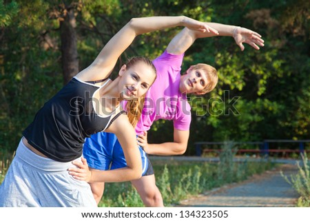 attractive couple runner stretching before their workout - stock photo