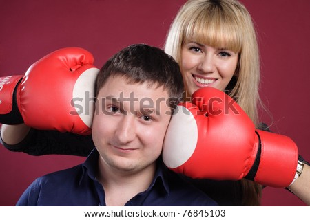 attractive family couple in  boxing gloves on red . cheerful young family have fun with boxing gloves.