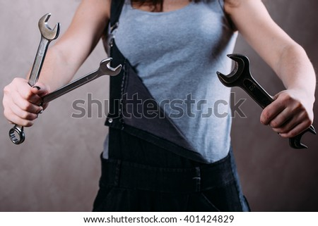 Attractive girl in dress working with the tools in the hands on a gray background - stock photo