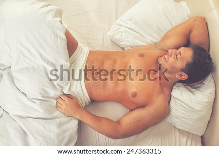 Attractive man lying in his bed smiling  - stock photo