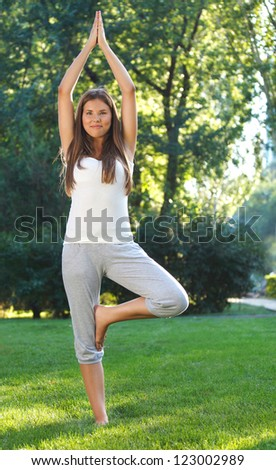 Attractive young woman doing yoga in summer park - stock photo