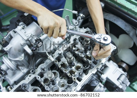 automotive mechanic tightening using a torque wrench - stock photo
