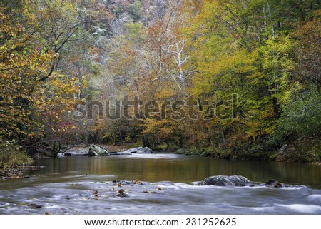 """""""Autumn Snow""""   A trace of snow can still be seen high above the Little River as it winds it's way through Great Smoky Mountains National Park in Tennessee. - stock photo"""