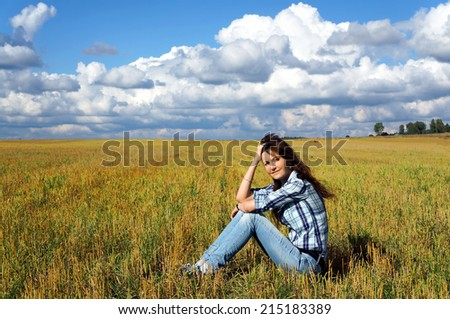 Autumnal nature; Yoing woman in haystacks on fields  - stock photo