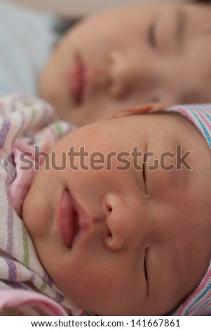 2 baby asian girls sleeping side by side - stock photo