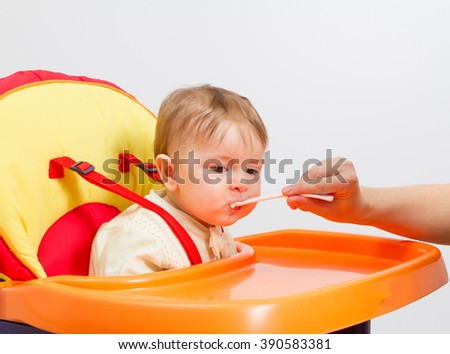 Baby boy eating with spoon at home in highchair - stock photo