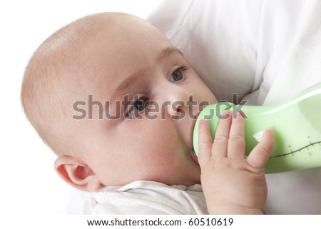 Baby boy looking at his parent while drinking from a baby bottle on white background