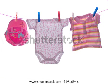 Baby clothes hang on clothesline - stock photo