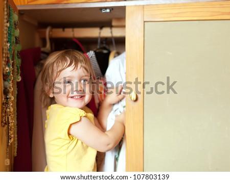 Baby girl  chooses dress in parent's closet - stock photo