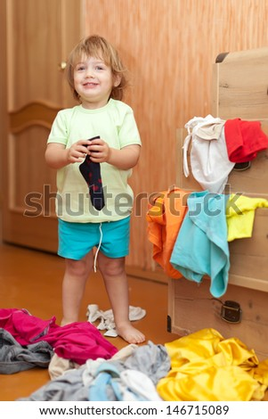 Baby girl  chooses dress in parent's wardrobe