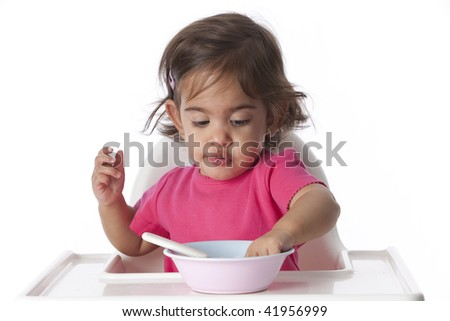 Baby girl is eating with her hand - stock photo