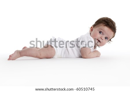 Baby girl lying on her belly full lenght on white background - stock photo