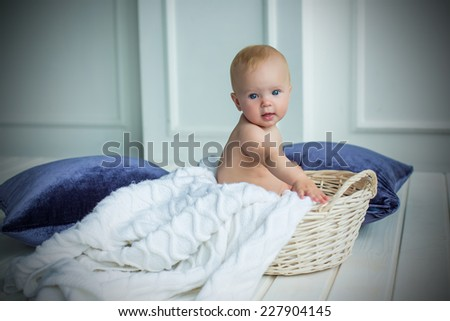 baby girl sitting in basket with white blanket in white interrior with violet pillows - stock photo