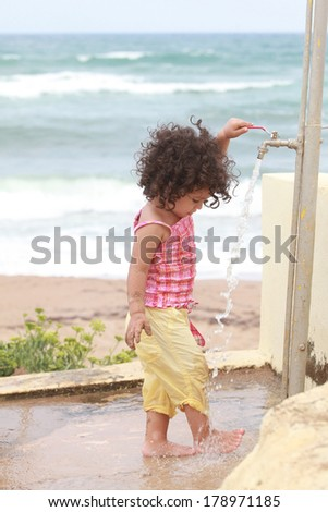 baby girl washing her feet  - stock photo
