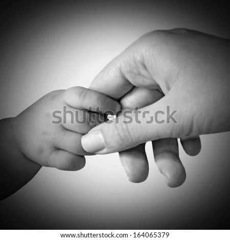 Baby hand gently holding mother's finger, black and white style - stock photo