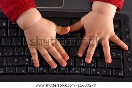 Baby hands on keyboard - stock photo