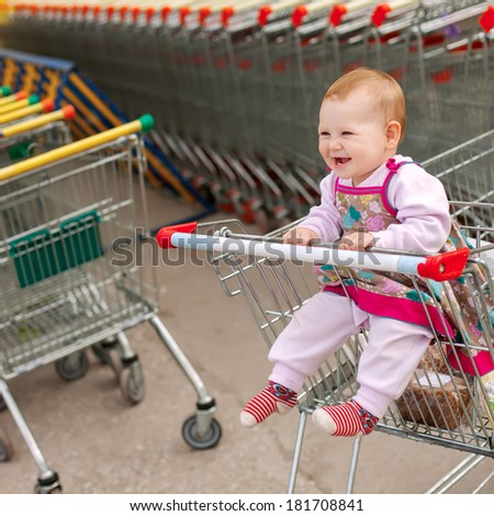 baby in shopping cart - trolley - stock photo