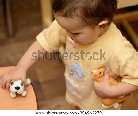 Baby kid toddler playing with toy animals  - stock photo