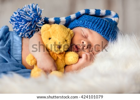 Baby newborn portrait, boy kid newborn sleeping in blue hat with teddy bear - stock photo