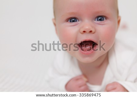 baby on a blanket with a big smile - stock photo